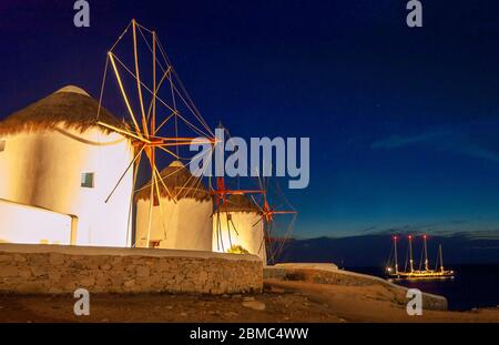 Illuminé de moulins à vent emblématiques sur l'île grecque de Mykonos sur la colline historique de Chora prise la nuit - Grèce Banque D'Images