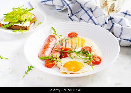 Petit-déjeuner anglais - œufs frits, saucisses, tomates et arugula. Cuisine américaine. Banque D'Images