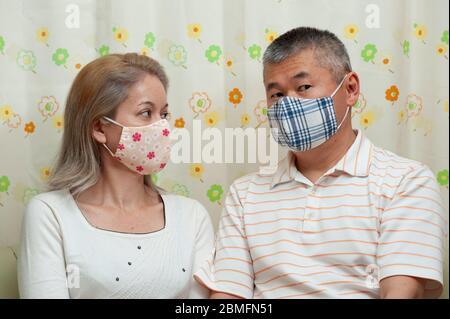 Couple d'âge moyen portant un masque facial en tissu de bricolage pour la protection contre le coronavirus (COVID-19) et d'autres maladies infectieuses. Banque D'Images