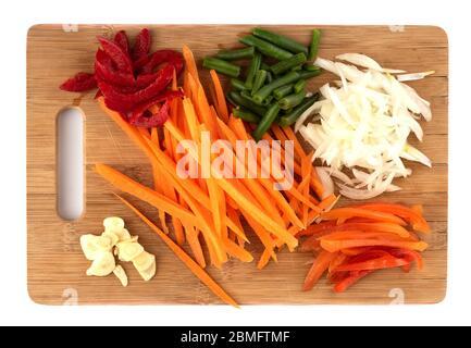 Tranches d'oignons, ail, carottes, poivrons doux sur une planche à découper. Tranches de légumes sur une planche à découper sur fond blanc. Pose à plat. Banque D'Images