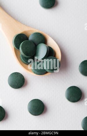 comprimés ronds verts de spiruline dans une cuillère en bois sur fond blanc gros plan vertical