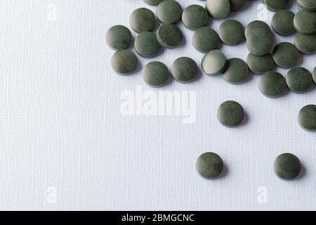 tablettes rondes vertes de spiruline sur fond blanc gros plan de l'espace de copie
