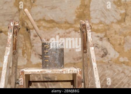 Un pinceau unique placé dans une vieille boîte de fruits recouverte de peinture et reposant sur une échelle de peintres anciens au soleil du matin Banque D'Images