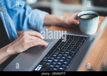 gros plan main de fille tenant le gobelet à café. Femmes d'affaires dactylographiant et défilement clavier sur ordinateur portable. Technologie femme concept de bureau