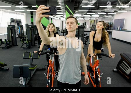 Beau petit homme canapé faire le selfie sur le téléphone dans la salle de gym, tandis que deux jeunes filles s'entraîner sur des vélos d'exercice ensemble dans le club de fitness Banque D'Images