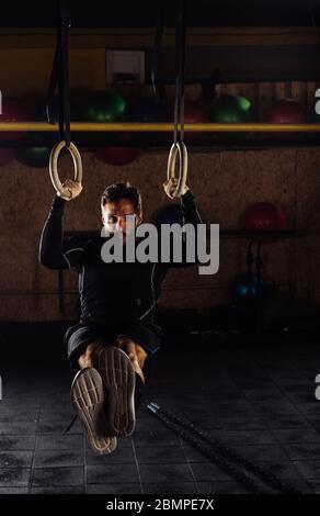 Mettre en place le jeune homme dans l'exercice de gymnastique noir sportwear avec joints toriques en salle de sport Banque D'Images