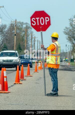 Un employé de la route tient un panneau d'arrêt pour diriger la circulation pendant qu'un équipage répare une route