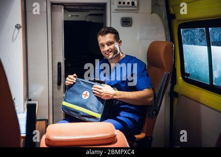 Un jeune homme paramédical assis dans une ambulance, tenant son kit médical et souriant à la caméra. Banque D'Images
