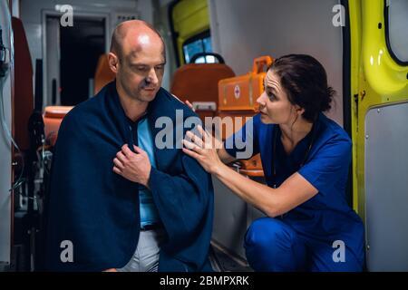 Une jeune femme en uniforme médical bleu qui tente de réconforter un homme blessé, assise sur le bord d'une voiture d'ambulance dans une couverture. Banque D'Images