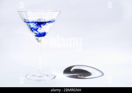 Une seule goutte de couleur bleu vif séparée de l'eau dans des verres martini transparents, Virginie, États-Unis, Amérique du Nord, couleur