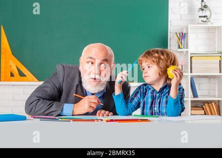 Homme mature enseignant et élève sur fond de babillard. Professeur principal en classe avec un enfant de l'école primaire. Élève et enseignant en classe Banque D'Images