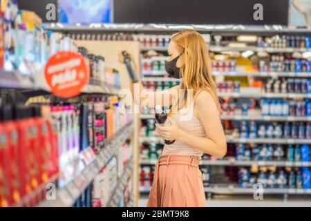 Une femme alarmée porte un masque médical contre le coronavirus lors de l'achat de produits chimiques domestiques dans les supermarchés ou les magasins, en santé, sécurité et pandémie