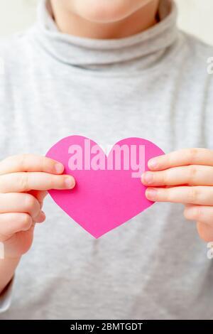 Gros plan de coeur rose dans les mains de petite fille sur fond blanc. L'enfant tient le cœur rose.