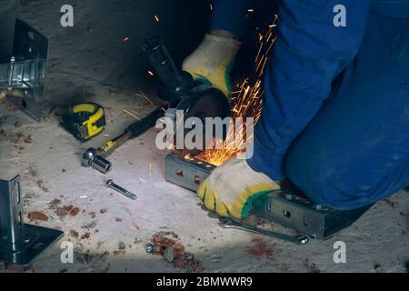 L'employé coupe le métal avec une machine à meuler. Flux de travail sur le chantier