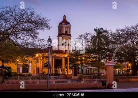 Place centrale avec kiosque et clocher de l'église Saint-Jean-Baptiste au crépuscule dans une ville coloniale bien préservée de Remedios, Cuba Banque D'Images