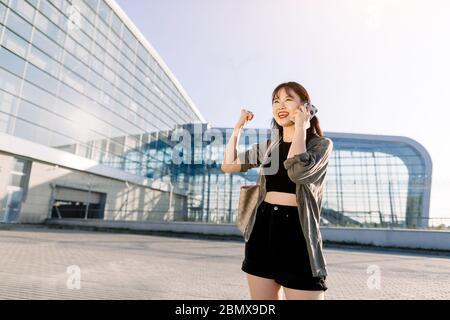 Chraming Happy asian brunette femme, vêtue de vêtements noirs décontractés, debout près de l'aéroport moderne ou de l'immeuble urbain avec la main levée et le poing de serrage
