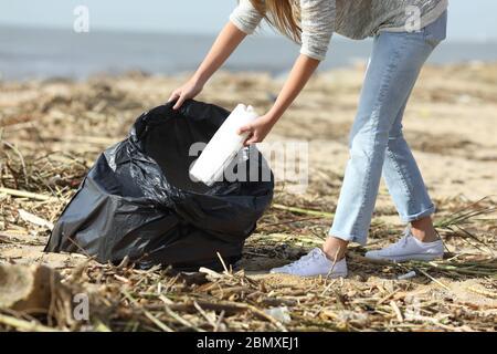 Gros plan d'un volontaire nettoyant une plage jetant une bouteille en plastique dans le sac Banque D'Images