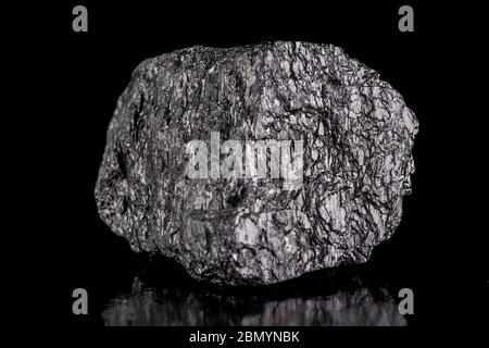Une masse de charbon brun posée sur une table. Minéral utilisé pour générer de l'énergie. Arrière-plan sombre. Banque D'Images