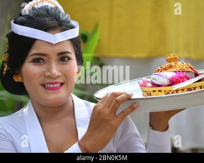 La femme indonésienne balinaise en blanc offre des offrandes lors d'une cérémonie religieuse de temple hindou et sourit pour la caméra.