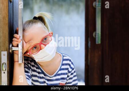 Un petit enfant qui a l'air malheureux et déprimé après avoir séjourné à la maison en raison d'activités interdites dans la rue. Enfant portant des masques médicaux vont dehors pour marcher dehors
