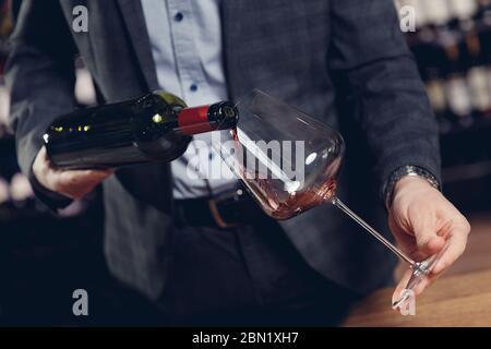 Un sommelier fait le vin rouge dans le verre sans éclaboussures Banque D'Images