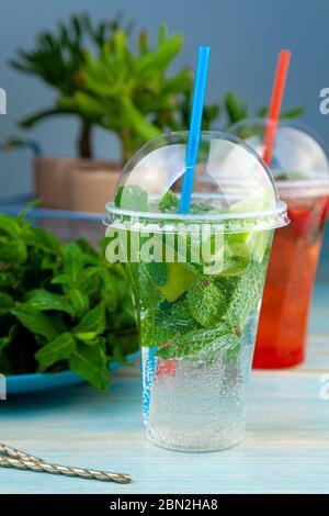 Mojito et Lemonade boisson froide d'été dans un verre de plastique avec une paille. Queue de cocon à la menthe, au citron, au citron vert et à la glace. Servir au bar. Gros plan sur les boissons.