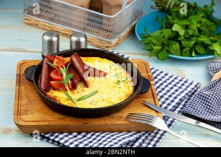 Omelette avec saucisse et tomates dans une casserole sur la table. Petit déjeuner appétissant. Une branche de romarin, une épice en bois. Chassez les saucisses. Plats savoureux frits Banque D'Images