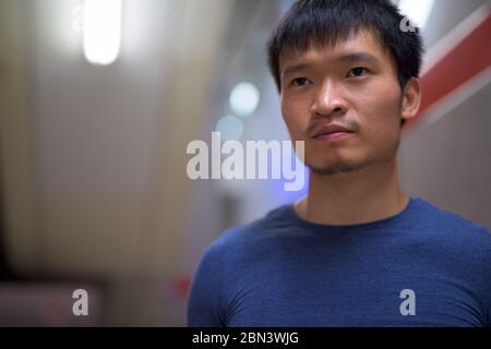Portrait d'un jeune asiatique à la station de métro Banque D'Images