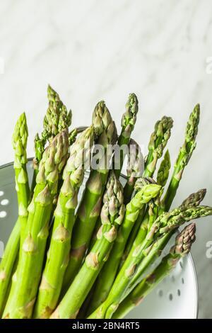 Asperges vertes fraîches. Légumes de saison sains dans la passoire. Banque D'Images