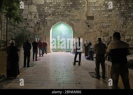 Jérusalem, ISRAËL, 12 mai 2020 : des fidèles musulmans palestiniens accomplissent la prière de Taraweeh pendant le mois sacré musulman du Ramadan, à l'extérieur de la mosquée fermée d'al-Aqsa dans la vieille ville de Jérusalem, dans le cadre de la pandémie COVID-19, le 12 mai 2020. La mosquée Al-Aqsa, située sur la place du Mont du Temple à Jérusalem, a été fermée il y a 51 jours par le Waqf, l'organisme religieux qui gère les lieux saints musulmans de la ville sainte, une mesure exceptionnelle visant à enrayer la pandémie du coronavirus. Banque D'Images