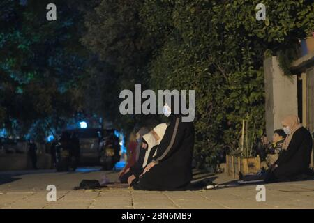 Jérusalem, ISRAËL, 12 mai 2020. Des femmes musulmanes palestiniennes adorantes qui effectuent la prière de Taraweeh pendant le mois sacré du Ramadan devant le complexe fermé de la mosquée al-Aqsa dans la vieille ville de Jérusalem, dans le contexte de la pandémie COVID-19, le 12 mai 2020. La mosquée Al-Aqsa, située sur la place du Mont du Temple à Jérusalem, a été fermée il y a 51 jours par le Waqf, l'organisme religieux qui gère les lieux saints musulmans de la ville sainte, une mesure exceptionnelle visant à enrayer la pandémie du coronavirus. Crédit : Eddie Gerald / Alay Live News Banque D'Images
