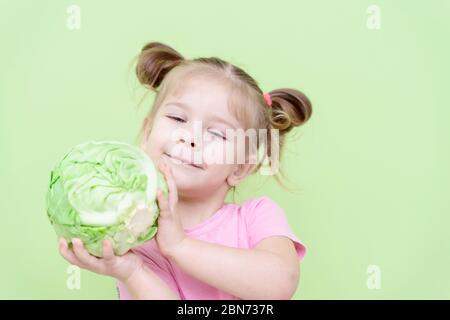 Petite fille de 4 ans dans un T-shirt rose sur un fond vert tenant un swing de chou dans ses mains et souriant. Alimentation appropriée pour les enfants d'âge préscolaire Banque D'Images