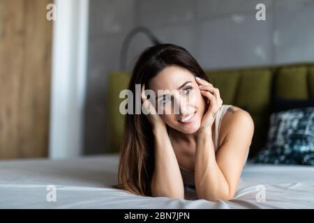 Pure beauté. Belle jeune femme ajustant ses cheveux et looking at camera couchée sur le lit à la maison