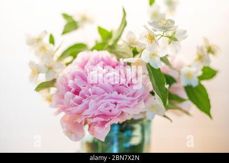 Bouquet de fleurs avec pivoine (paeonia) et fausse-orange (philadelphus), plantes printanières. Fond rose et blanc, gros plan. Banque D'Images