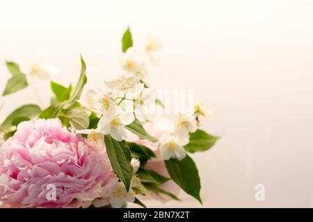 Le fond des fleurs printanières est rose et blanc, avec pivoine (paeonia) et orange mock (philadelphus). Fond d'écran bouquet gros plan avec espace de copie sur la droite Banque D'Images