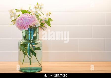 Bouquet de fleurs avec pivoine (paeonia) et orange maquette (philadelphus), dans un vase en verre bleu avec des carreaux blancs dosseret en arrière-plan. Banque D'Images