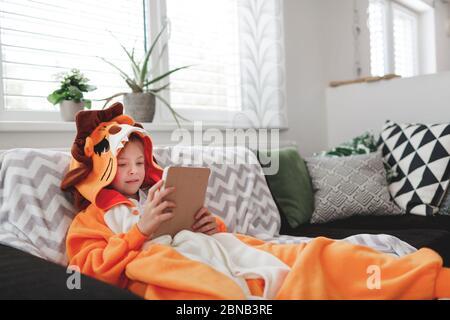 Belle jeune fille avec costume de lion joue avec un téléphone mobile ou une tablette