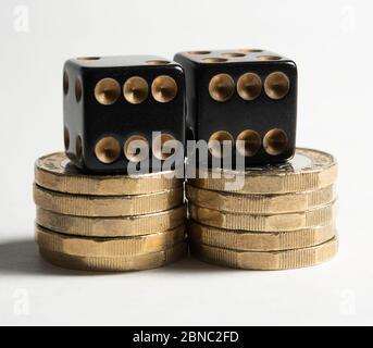 Deux dés noirs sur des piles de pièces d'une livre contre un concept de jeu de fond blanc Banque D'Images