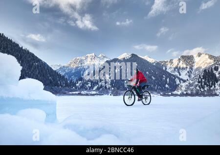 L'homme en veste rouge est à vélo sur un lac gelé à des montagnes enneigées en arrière-plan