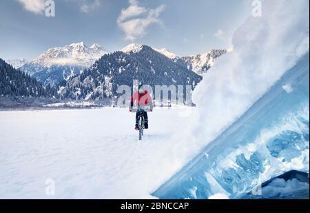 L'homme en veste rouge est à vélo sur un lac gelé avec de la glace bleue au premier plan à des montagnes enneigées en arrière-plan