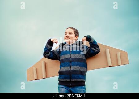 Garçon rêve de devenir aviateur. Enfant jouant avec des ailes d'avion