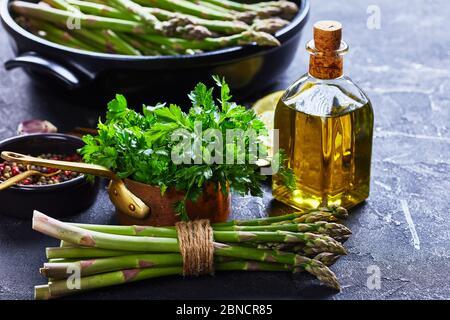 gros plan d'un bouquet d'asperges vertes fraîches avec plat à pâtisserie noir, bouteille d'huile d'olive à l'arrière-plan, vue horizontale depuis le dessus