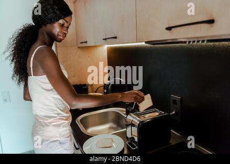 Femme afro-américaine mettant des morceaux de pain dans le grille-pain et souriant dans la cuisine Banque D'Images