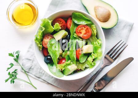 Salade fraîche d'avocat, de cerise, d'arugula et d'olives faites à la maison. Banque D'Images