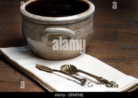 Bol en poterie vintage avec cuillères anciennes sur une serviette de table en bois Banque D'Images