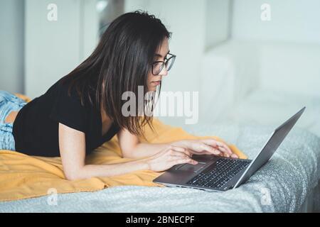Jolie femme brune portant des lunettes et travaillant sur un ordinateur portable. Femme concentrée couchée au lit à la maison écrivant et utilisant le clavier d'ordinateur portable