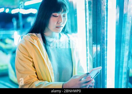 Bonne fille asiatique utilisant un smartphone au parc d'attractions - jeune femme tendance s'amusant avec des tendances tecnologiques avec des néons dans les milieux - Tech et jeunesse c