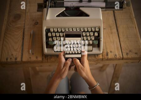 Concept, écriture et travail avec une technologie ancienne et moderne, nouvelle, femme prend une photo d'une machine à écrire avec son téléphone cellulaire