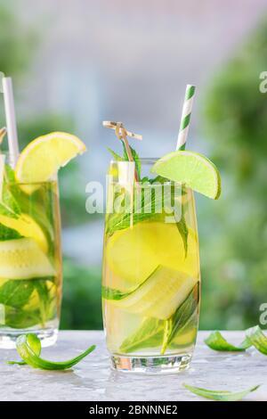 Deux verres de limonade ou de mojito cocktail avec citron, concombre et menthe, boisson rafraîchissante froide ou boisson avec glace et paille de papier, extérieur. Été