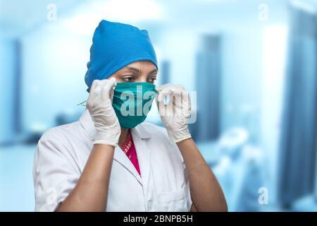 Gros plan d'une travailleuse médicale, infirmière mettant sur un masque chirurgical de respirateur pour protéger contre le coronavirus, Covid-19 pandémie. Banque D'Images